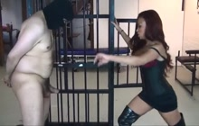 Hot ebony mistress releases her slave from cage for ballbusting